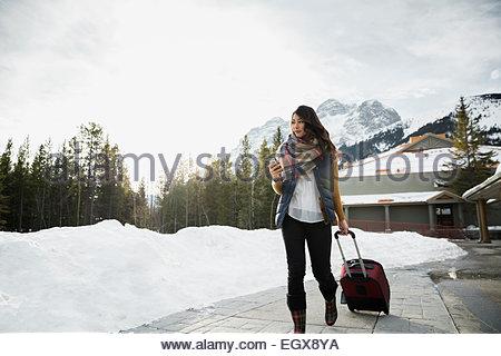 Woman pulling suitcase on sidewalk below mountains - Stock Photo