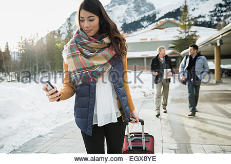 Woman pulling suitcase on sidewalk below mountains - Stock Photo