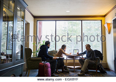 Business people working at laptop in lobby - Stock Photo