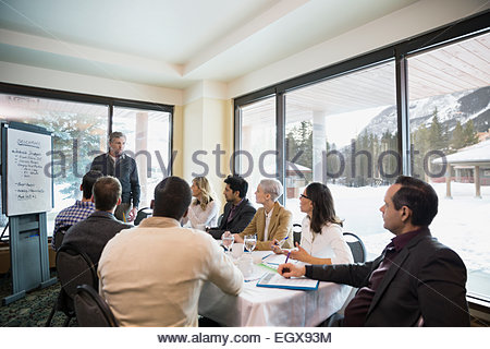 Businessman at flipchart leading meeting in conference room - Stock Photo
