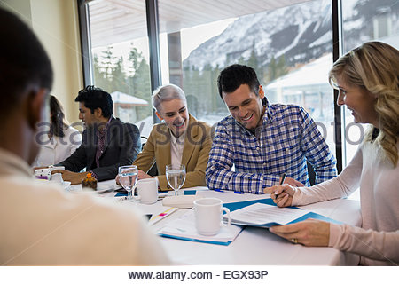 Business people reviewing paperwork at conference table - Stock Photo