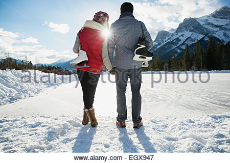 Couple with ice skates hugging below snowy mountain - Stock Photo
