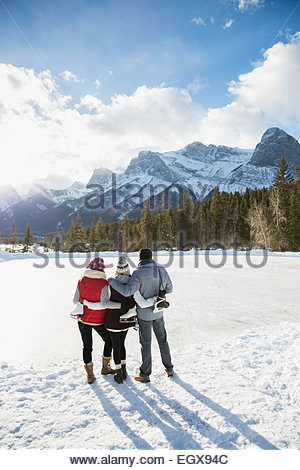 Family with ice skates hugging below snowy mountain - Stock Photo