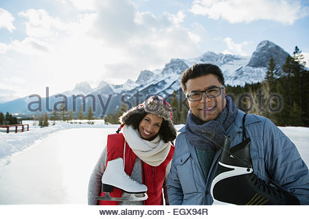 Portrait of couple with ice skates near mountain - Stock Photo