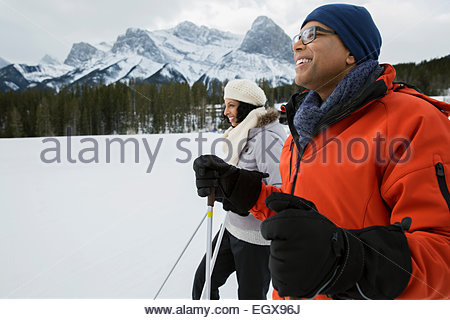 Smiling couple cross-country skiing in snowy field - Stock Photo