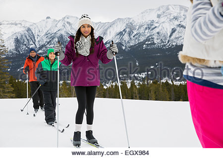 Family cross-country skiing in snowy field - Stock Photo
