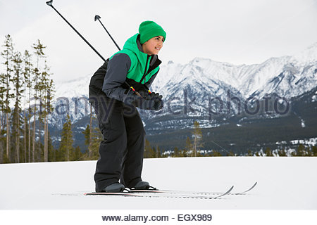 Boy cross-country skiing in snowy field - Stock Photo