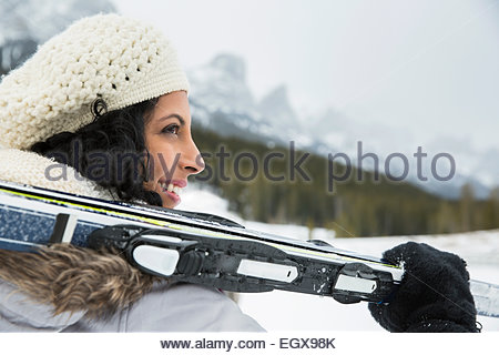 Smiling woman holding skis below snowy mountains - Stock Photo