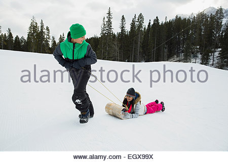 Boy pulling sister on sled in snowy field - Stock Photo