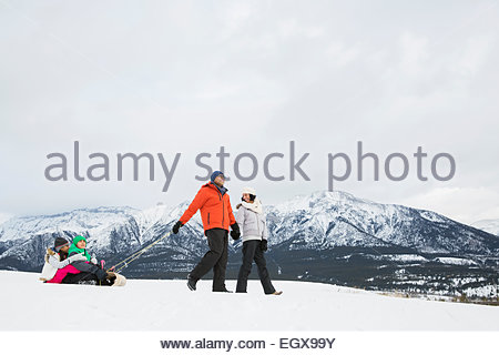 Parents pulling children on sled in snowy field - Stock Photo