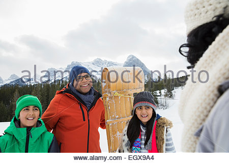 Family with sled in snowy field - Stock Photo