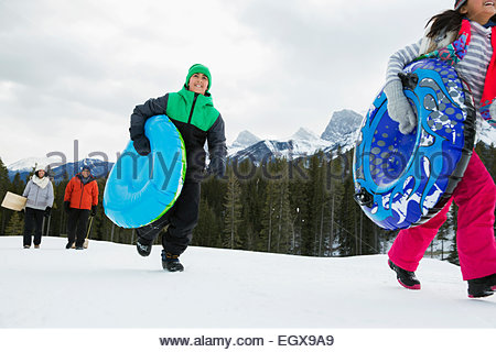 Family with inner tubes in snowy field - Stock Photo