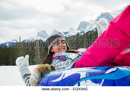 Girl playing on inner tube in snow - Stock Photo