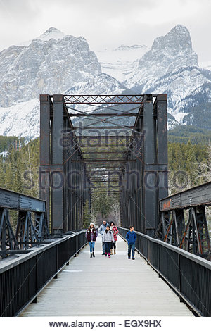 Family walking along bridge below snowy mountains - Stock Photo