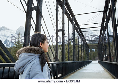 Girl walking along bridge below snowy mountains - Stock Photo
