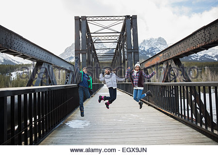 Brother and sisters jumping on bridge below mountains - Stock Photo
