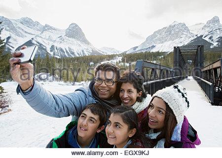 Family taking selfie below snowy mountains - Stock Photo