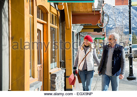 Couple in warm clothing walking along storefront - Stock Photo