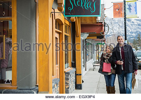 Couple with shopping bags walking outside storefront - Stock Photo