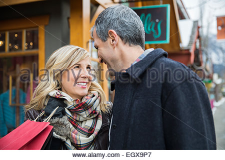 Smiling couple with shopping bag outside storefront - Stock Photo