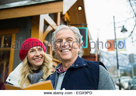 Smiling couple with map outside storefront - Stock Photo