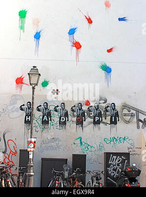 Several kinds of graffiti on building wall in Paris, France. Cloned male images bear  letters and have gun to their - Stock Photo