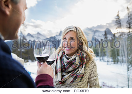 Couple toasting wine glasses with mountains in background - Stock Photo