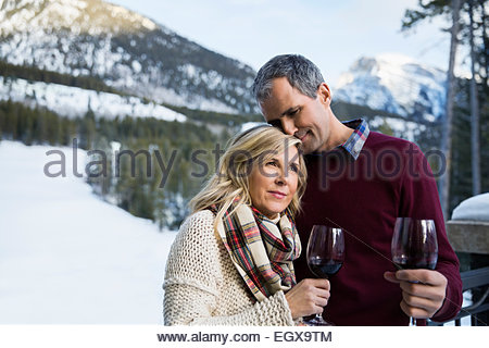 Couple drinking wine with snowy mountains in background - Stock Photo