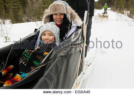 Portrait of mother and daughter in dogsled - Stock Photo