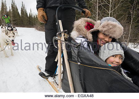 Portrait of smiling mother and daughter in dogsled - Stock Photo