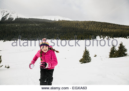 Portrait of smiling girl with snowball in field - Stock Photo