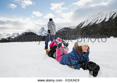 Family sledding in snowy field below mountains - Stock Photo