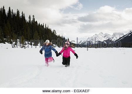 Girls running in snowy field below mountains - Stock Photo