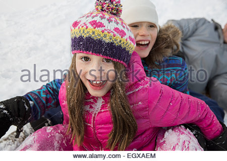 Portrait of smiling girls playing in snow - Stock Photo