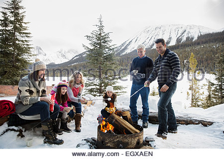 Multi-generation family roasting marshmallows at fire pit - Stock Photo