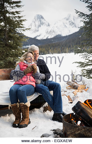 Couple relaxing at fire pit in snow - Stock Photo