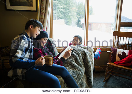 Family reading and relaxing in lodge living room - Stock Photo