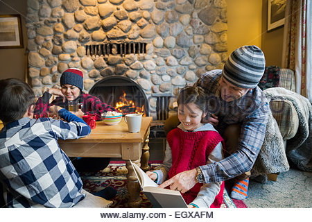 Family playing chess and reading in living room - Stock Photo