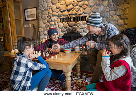 Family playing chess in lodge living room - Stock Photo