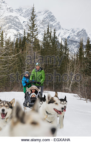 Family dogsledding below snowy mountain - Stock Photo