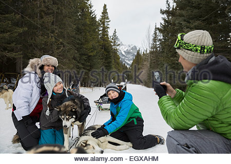 Family petting dogsled dogs in snow - Stock Photo
