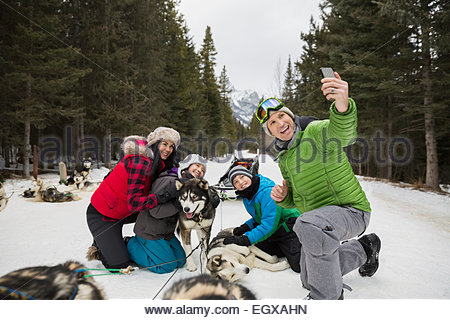 Family taking selfie with dogsled dogs in snow - Stock Photo