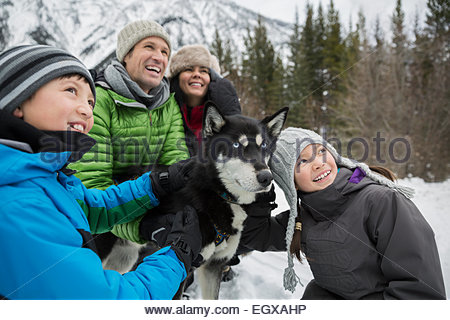 Smiling family with dogsled dog in snow - Stock Photo