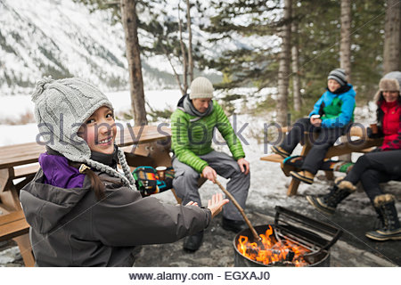 Family relaxing around fire pit - Stock Photo