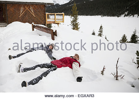 Sisters making snow angels in snow outside lodge - Stock Photo