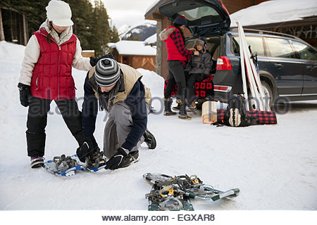 Father fastening snowshoes on daughter in snowy driveway - Stock Photo