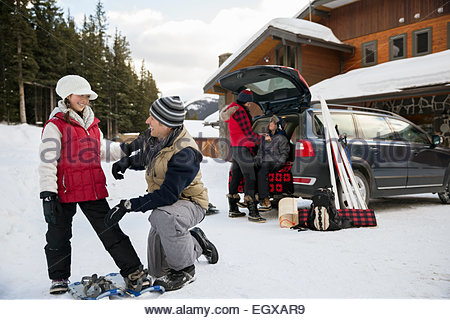 Father and daughter putting on snowshoes in driveway - Stock Photo