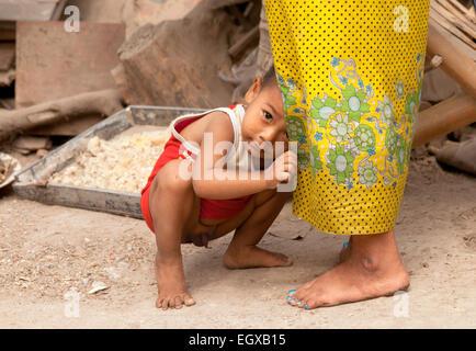 Shy infant burmese boy hiding in his mothers skirt, Mandalay, Myanmar ( Burma ), Asia - Stock Photo