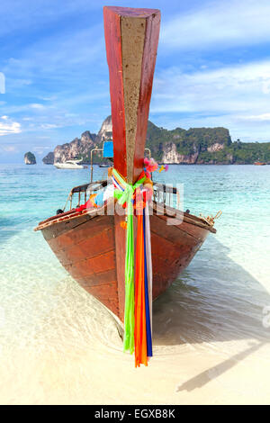 Old traditional wooden boat on a tropical island in Thailand. - Stock Photo