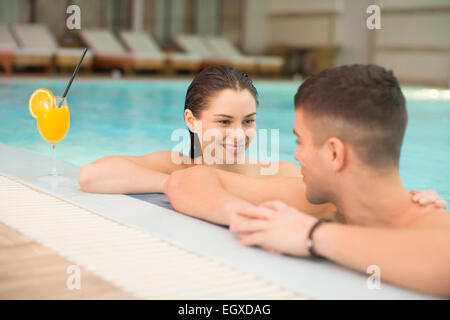 Young couple relaxing in the swimming pool - Stock Photo